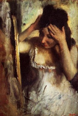 woman combing her hair in front of a mirror
